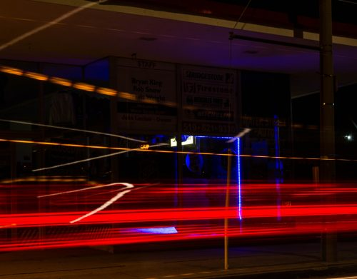 Cars pass by an automobile store on Water St at night